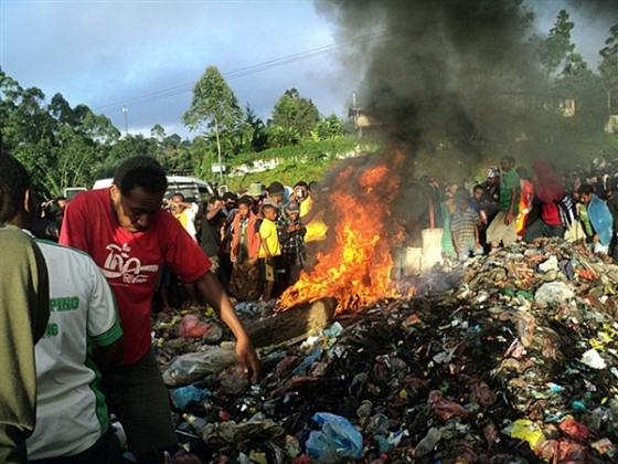 Bystanders watch as a woman accused of witchcraft is burned alive in the Western Highlands provincial capital of Mount Hagen in Papua New Guinea. Photo: Post Courier via AP